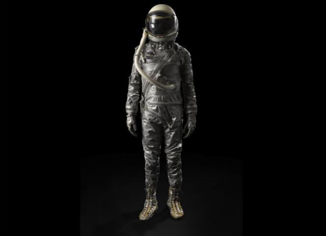 """MERCURY ERA SPACESUIT. Cover layer from a Phase 2 Mercury era space suit, with early model """"widow's peak"""" helmet and gloves.  Est. $8,000-12,000"""